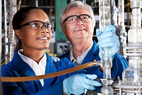 Young female immigrant, dark hair, safety glasses, smiling, holding laboratory equipment with blue gloves, next to smiling German mentor, male, smiling, white hair, both benefitting from programs administrated by the German Integration Foundation