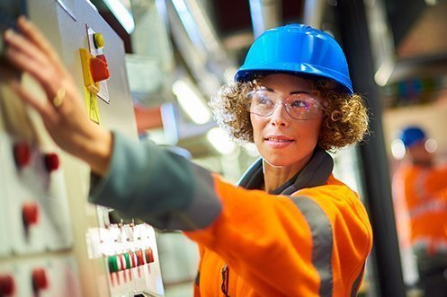 Woman in hard hat, wearing safety glasses, curly hair, reaching over to a power plant panel, happy she has one of the fastest growing Louisiana Jobs