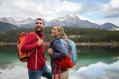 Handsome man with brown hair, mustache and beard, wearing a red jacket, holding an orange backpack, looking up and smiling, standing next to blonde woman wearing blue jacket and holding a blue backpack, set for ecotourism event, both have new jobs in Ontario province due to the new immigration pilot initiative