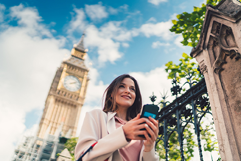 Smiling woman with dark hair, holding phone, in front of Big Ben in London, happy that British Workers Fill Jobs