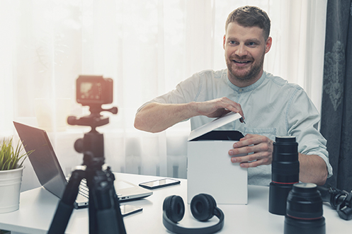 Smiling handsome man, with beard, opening box in front of camera, is a home seller recording a household goods video survey