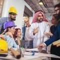 Group of 8 male and female workers, sitting or standing around a table with drawings, several wearing hard hats, talking with a Saudi Arabia citizen, all benefits of the Special Privilege Iqama