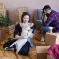 Woman with dark hair, smiling, wearing a dark shirt, holding white pet dog, man with dark hair and beard behind her, wearing a red and blue checked shirt, unpacking boxes, just received their dog after a pet move