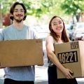 Man with dark hair, glasses, beard and mustache, smiling, carrying a box, woman with red hair, glasses, smiling carrying a box, helping out with Summertime Household Goods Moves