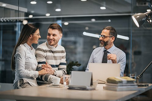 Woman with long dark hair wearing glasses and white shirt, smiling, holding arm of man with short hair, beard and mustache, wearing a striped sweater, smiling, with man to the right wearing glasses, with full beard, wearing shirt and tie, Realtor® asks relocating employees questions about their coming move