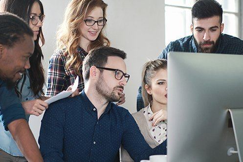 Group of six information technology coworkers, three men, three women, all looking at a computer screen, programming a new relocation API