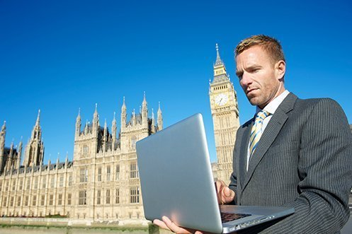 Male banker holding laptop in front of Big Ben in the background, wearing a suit, looking at laptop, planning on relocating UK workers