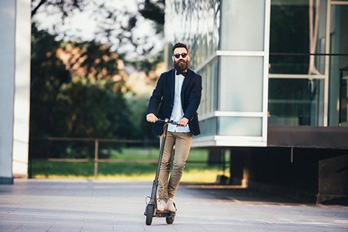 Handsome man with beard, mustache, and sunglasses, wearing a bow tie, white shirt, and jacket, facing forward, riding an e-scooter in compliance with new Los Angeles city regulations
