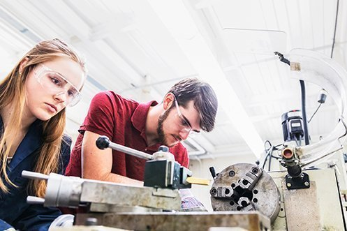 Blonde Gen Z woman wearing safety glasses, Gen Z man with dark hair and beard wearing safety glasses, both working at manufacturing industry opportunities