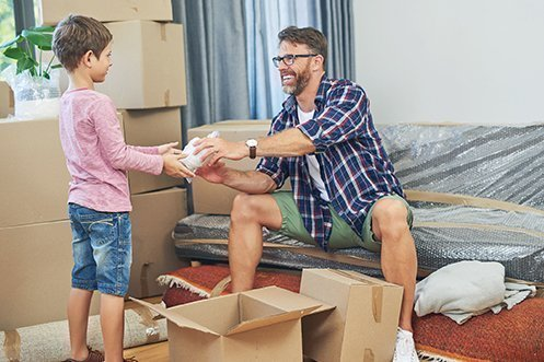 Young boy with pink shirt handing item to man with beard and eyeglasses, who is smiling and wearing a blue and white check shirt, green shorts, and white t-shirt, as they pack for their small shipments household goods move