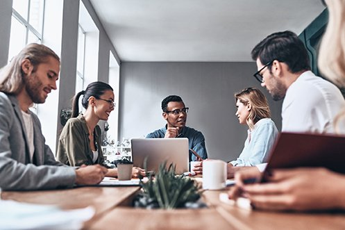 Three men and three women, one woman is partially out of the image, working as a project team around a table to determine the company's year-end relocation expense reconciliation