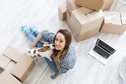 Woman with dark hair, looking up from floor with moving boxes and computer, dog on her lap licking her face, using relocation technology features to help her move