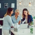 Three business colleagues talking together looking at a paper standing at a work table, woman with long hair and blue shirt, woman with short hair and blue shirt, and woman with long hair and dark blue jacket all reviewing domestic short term assignments best practices