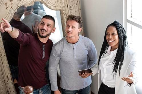 2020 US Rental Market benefits man with black hair, mustache and goatee, wearing red shirt, and his male partner with curly brown hair, mustache and goatee, wearing gray shirt, both smiling and looking up at a feature in a rental unit, with woman rental leasing agent also looking, smiling, wearing white shirt and white jacket, holding a smartphone