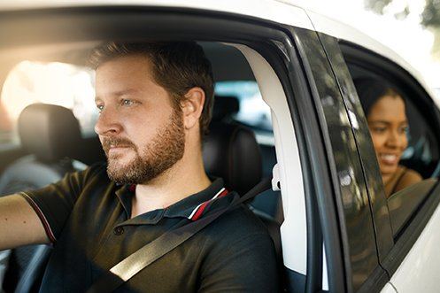 Handsome male car driver at wheel of white shared ride car, facing forward, with brown hair, beard, and mustache, wearing a black shirt, woman passenger in back seat looking out the window, smiling