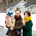 Man in brown coat with red scarf, brown hair, mustache and beard, holding small child in his arms, woman with brown hair, all smiling, standing in front of house they bought from winter home sellers