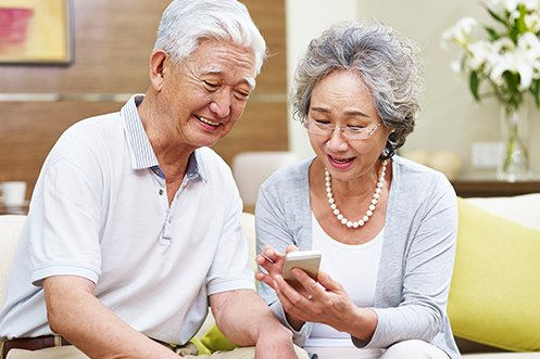Older Japanese man and woman smiling, looking at phone, discussing how aging impacts country demographics