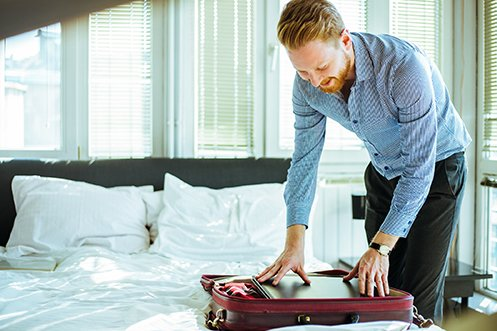 Male traveler with red hair and beard, wearing dark pants and blue shirt, packing his suitcase and taking prudent business traveler health precautions