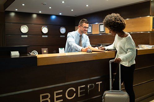 Man with short hair and glasses, smiling, a front hotel desk worker helping a female business traveler with suitcase and white sweater check in to her room, the man is a new hire as noted in the January 2020 jobs report