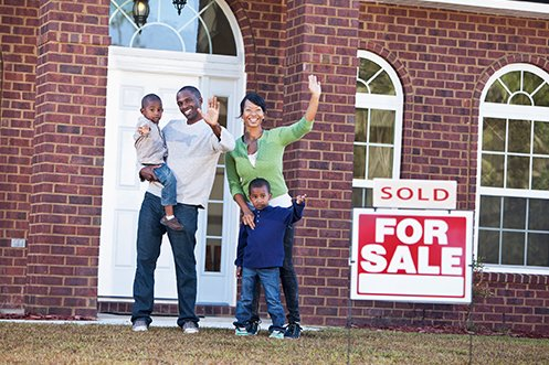 Smiling father and mother with two children, waving happily in front of their home and grateful for bvo program benefits, for sale sign with sold placard in front, brick house behind