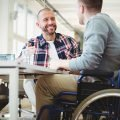 Man wearing plaid shirt over white t-shirt, smiling, facing disabled man in wheelchair, both working at same company that has inclusive employment goals to promote hiring of those with disabilities, veterans, and those formerly incarcerated