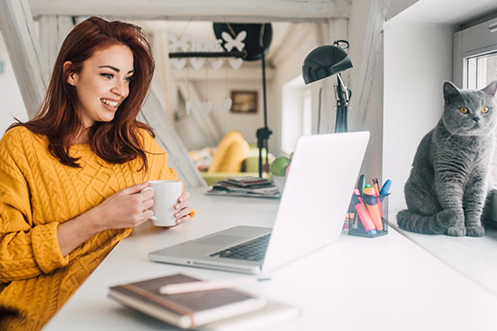 Woman with dark hair wearing a yellow sweater looking at computer working from home