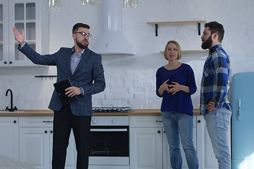 Man with beard and dark hair, licensed professional appraiser with glasses and blue jacket, talking to two homeowners, a woman in blue shirt with blonde hair and a man in blue check shirt with dark hair and beard, about their home relocation appraisal