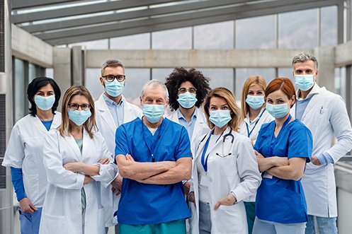 Group of nine healthcare workers, five women and four men, all wearing masks and facing forward, benefitting from healthcare corporate housing solutions