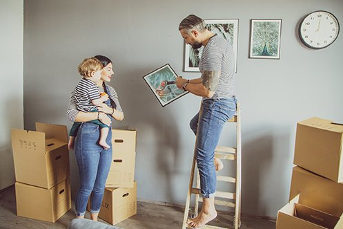 Man wearing blue jeans and striped t-shirt, with gray hair and dark beard, standing on a ladder, woman with dark hair holding a child in her arms, man is hanging photos on wall after their move during COVID COVID-19