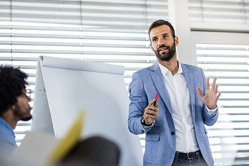 Handsome man with dark hair, mustache, and beard, wearing a white shirt and blue jacket, providing successful language training to group of students