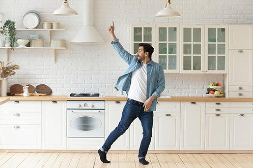 Handsome man with dark hair, mustache and bears, wearing blue jeans, white t-shirt and blue shirt, black socks, no shoes, dancing in kitchen, working from home and doing his best at beating isolation