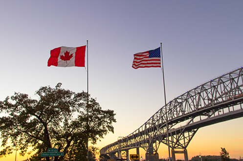 Canada and USA flags flying along bridge at international border which faces border restrictions