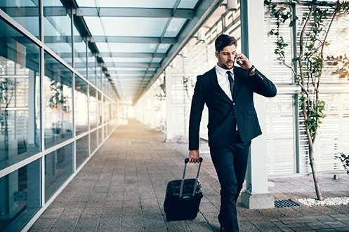 Male business traveler with dark hair, mustache and beard, wearing a suit and a tie, talking on a cell phone, walking through an airport with other short-term domestic business travelers