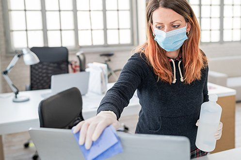 Woman with long brown hair, wearing face mask and gloves, cleaning a computer screen as she prepares for her company's returning workforce