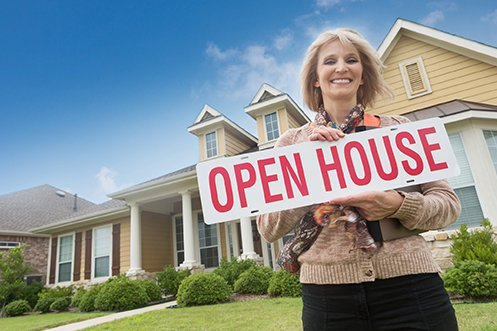 Female real estate agent holding open house sign in the middle of creating virtual agent services