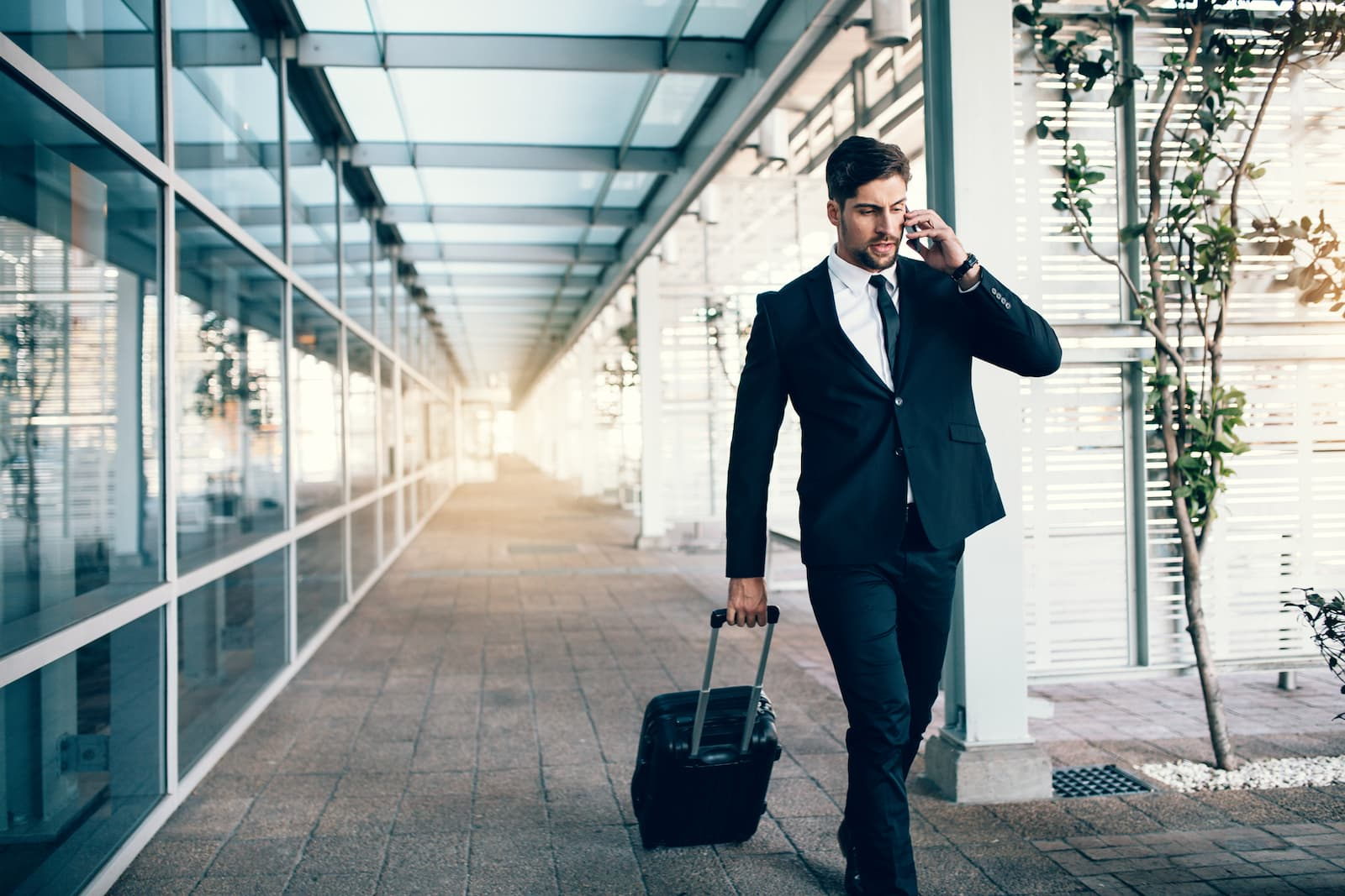 Businessman walking through airport during a short-term travel stay