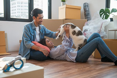 Man sitting on floor, woman laying on floor, holding up family cat, moving boxes around them, they just moved into their new apartment and had to arrange animal transportation so their cat could be with them as they flew from one state to another for a new job