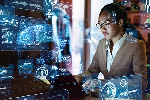 Female engineer working on computer with graphics, wearing glasses and tan coat, employer had to pay higher immigration application fees to bring her to the US