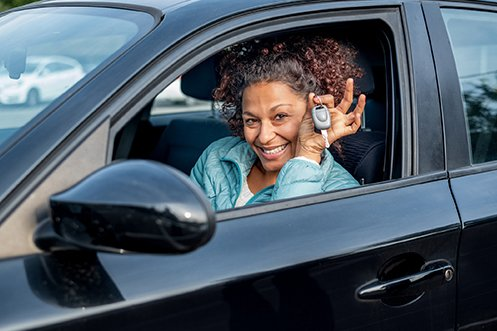 Woman driver in car with curly hair, wearing a blue shirt, holding up keys, smiling and happy with her flexible transportation solution