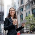 Businesswoman wearing blue jacket, eyeglasses, holding a cup of coffee and tablet, standing on street in London, smiling, benefitting from the US and UK totalization agreements