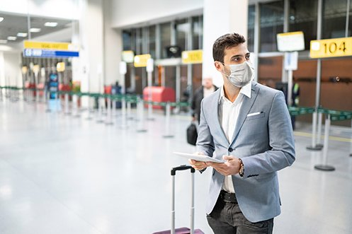 Man wearing mask at airport, with blue jacket, dark pants, white shirt, looking at a tablet, next to luggage, with dark hair, determine his best option for airline travel
