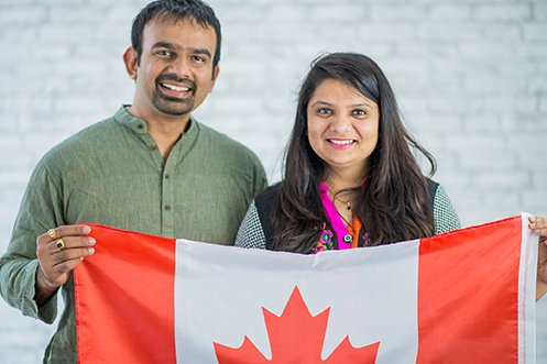 India man and woman, both foreign nationals, facing forward, smiling, holding up a Canadian flag, hired by a US employer under Canada immigration alternatives