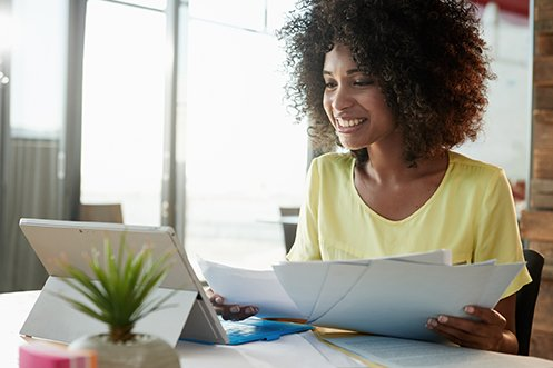 Woman smiling, with dark hair, holding paperwork in front of a computer, reviewing her company's 2020-21 Corporate Relocation Budget
