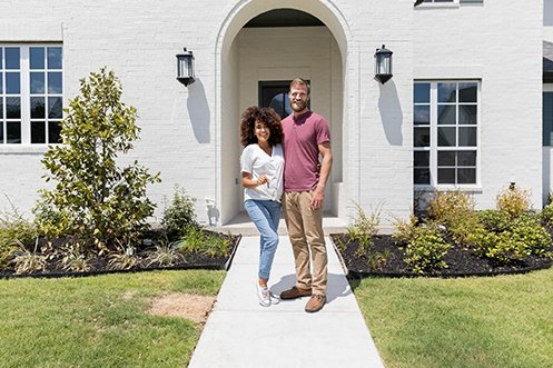 Woman in white shirt with dark curly hair, many in red shirt and tan pants, blonde/brown hair and full beard, young couple in front of house holding keys, happy they looked at renting versus buying and chose to buy this beautiful home