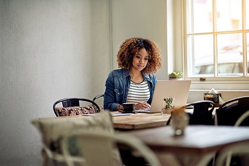Woman with dark curly hair, working at her kitchen table, wearing a blue jean jacket and white striped shirt, smiling, looking at her laptop, benefitting from her employer's work from anywhere policies