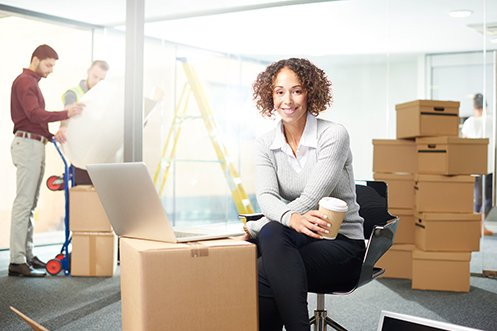 Woman with dark curly hair sitting at computer, smiling and facing forward, wearing a gray sweater and black pants with a white shirt, holding a coffee cup, surrounded by boxes and a yellow ladder behind her during a move, and she is looking through the Corporate Relocation Factors that the company considered for its relocation
