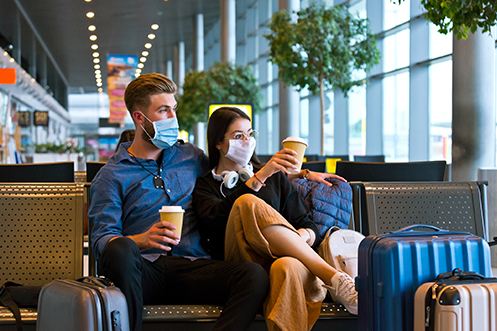 Man and woman sitting in airport, both wearing masks, both holding coffee cups, man is wearing a blue shirt and black pants, woman is wearing a black shirt and tan pants, both are looking out the window, following COVID-19 travel recommendations
