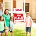 Mother, father, two daughters and one son standing in front of their new home with a Sold sign on it in one of the 2020 fastest selling housing markets