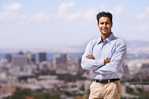 Smiling male employee, wearing blue shirt and tan pants, dark hair, standing on balcony overlooking a city, benefiting from his 2020-21 employee relocation package to a city he wants to live in