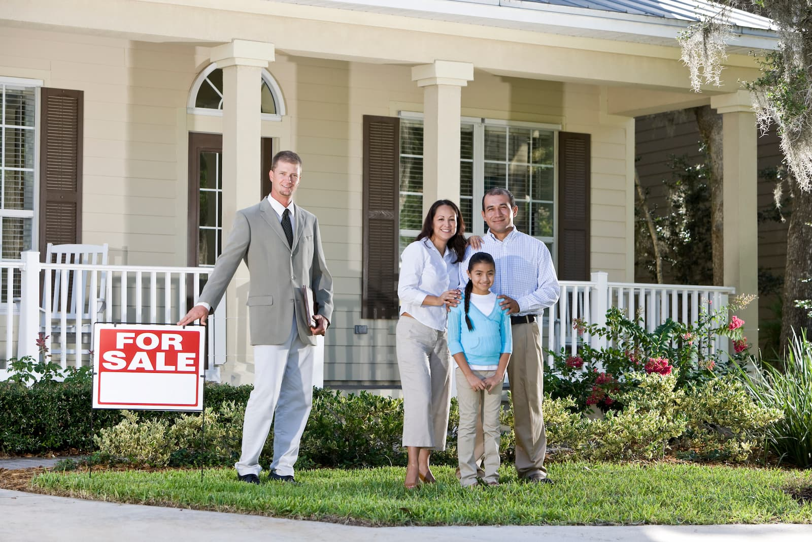 A family with the realtor in front of the house they just had appraised